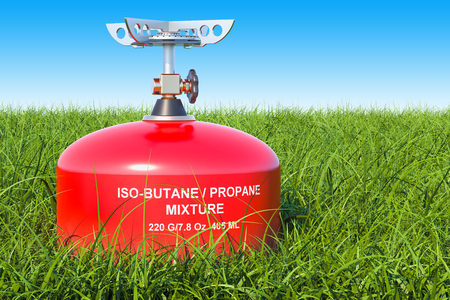 Red primus stove on the green grass against blue sky, 3D rendering Stock Photo - 100474137