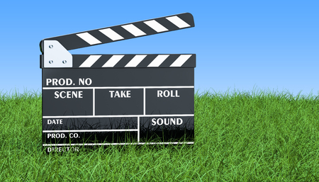 Movie clapper board on the green grass against blue sky, 3D rendering