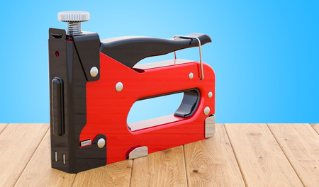 Staple gun, 3D rendering on the wooden table. 3D rendering