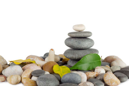 Pyramid of the round sea stones with leaves isolated on white background