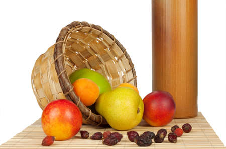 Fruit spill out of the basket on a bed of straw isolated on white background photo