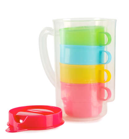 Four colorful cups with pitcher isolated on white background photo
