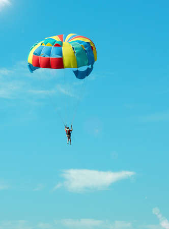 Bold paratrooper flying in bright parachute in the sky photo