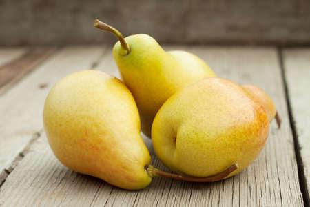 Three ripe yellow pears on a wooden background Standard-Bild