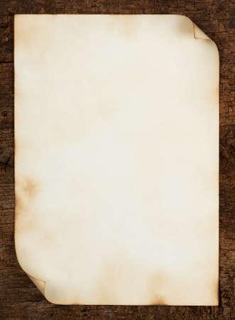 curled edges: Vecchio foglio di carta con bordi arricciati sul fondo in legno