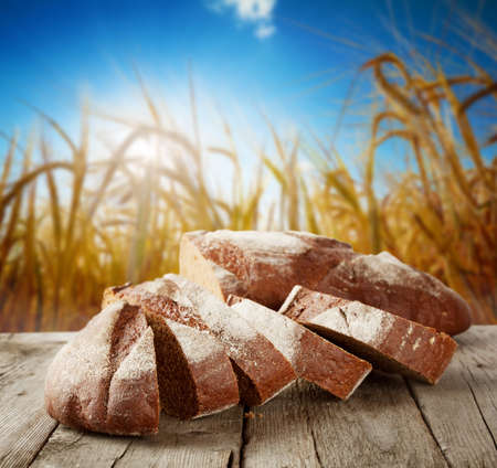 Sliced loaf of bread on the background of wheat photo