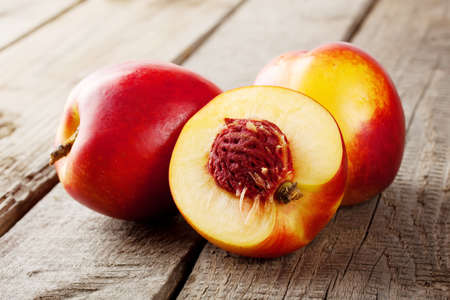 Three ripe juicy nectarine on a wooden background