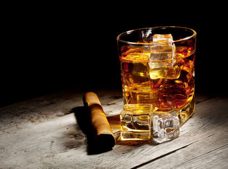 Glass of aged whiskey with cigar and ice cubes on wooden table