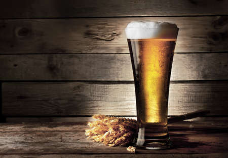 Tall beer glass with beer and ears on wooden background 版權商用圖片