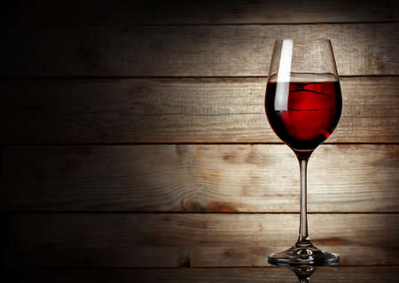 Glass of red wine on a young wooden background