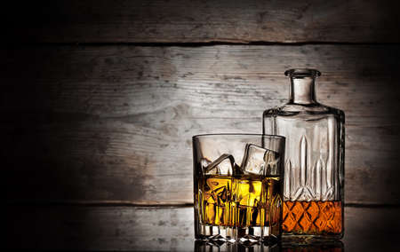 Glass of whiskey with ice cubes and faceted bottle on a wooden background