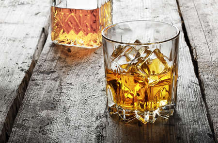 Faceted glass of whiskey with ice and a decanter on a wooden table Standard-Bild