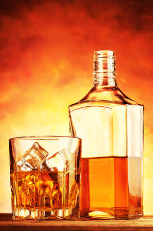 Noble whiskey in a glass and bottle on a wooden table