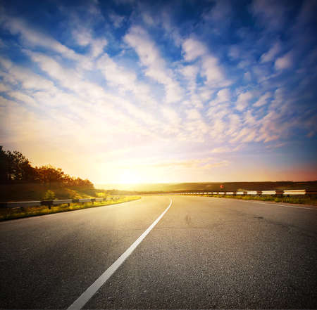 Evening landscape with a road going into the horizon at sunset sky