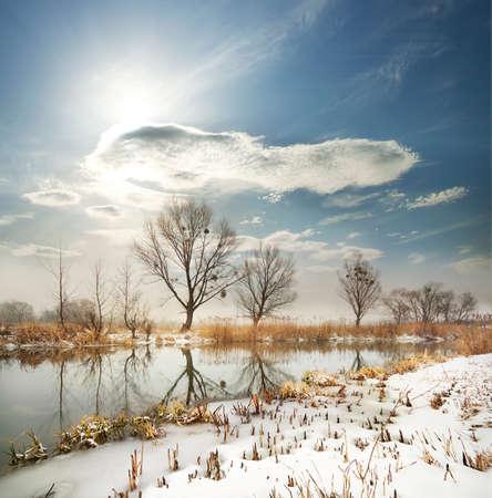 shores: Winter river with the frozen shores under a cloudy sky Stock Photo