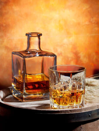 Bottle and glass of whiskey with ice on a wooden barrel
