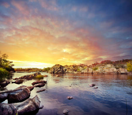 rifts: Mining fast river under dramatic sunset sky