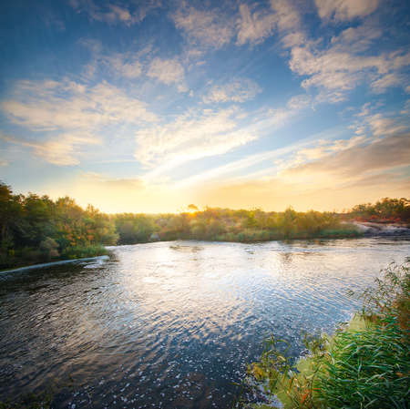rifts: Dawn on the river flowing in the forest under the beautiful sky Stock Photo
