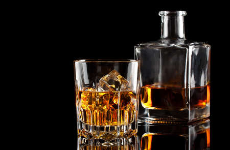 Glass of whiskey with ice and a square decanter isolated on a black background