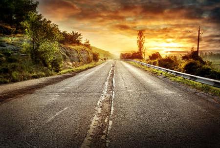 under fire: Carretera de asfalto que retrocede en la distancia bajo un cielo dramático de fuego Foto de archivo