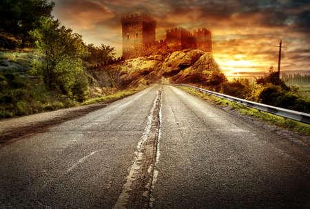 under fire: Carretera de asfalto que retrocede en la distancia bajo un cielo dram�tico de fuego Foto de archivo