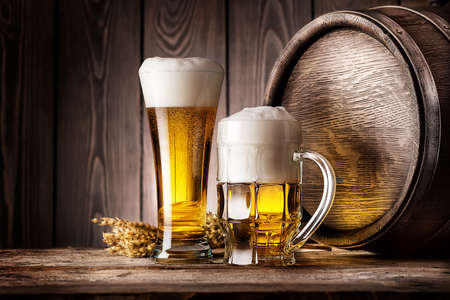 Mug and a glass of light beer with ears of barley and wooden barrel