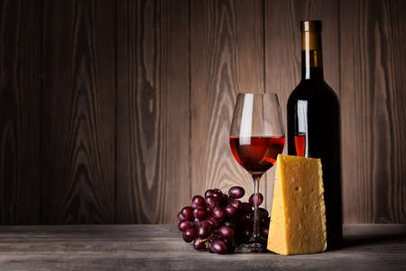 Glass of red wine with grapes and cheese on a wooden background