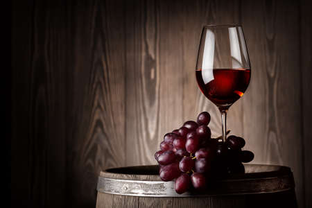 Glass of red wine with grapes on wooden barrel at the wooden wall Standard-Bild
