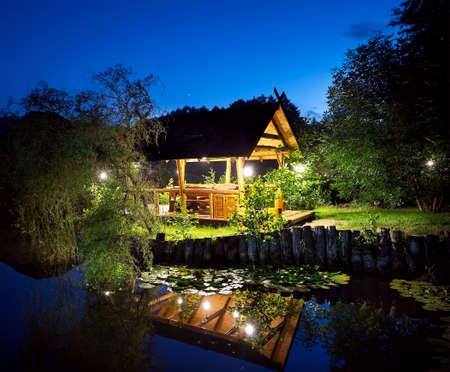 Wooden gazebo lit lanterns on the lake under the night sky 免版税图像