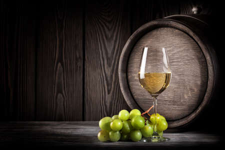 Glass white wine and bunch grapes on background of wooden barrels Standard-Bild