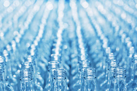Number empty glass bottles on conveyor with blurred background