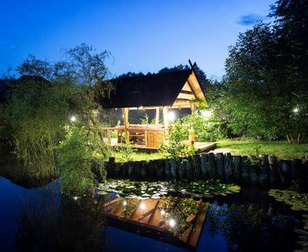architectural lighting design: Wooden gazebo lit lanterns on the lake under the night sky Stock Photo