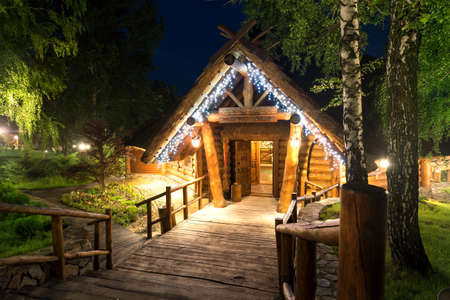 architectural lighting design: Wooden cottage in forest lit by lanterns at night