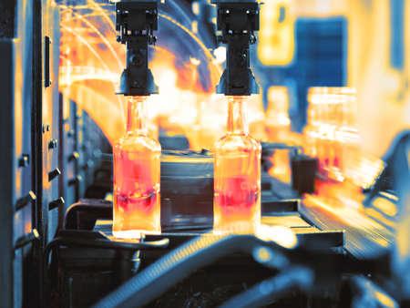 Moving assembly line for production of glass bottles shot in motion Standard-Bild