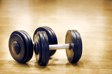 heavy effect: Two dumbbells on the floor in hall Stock Photo