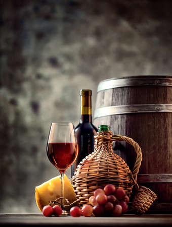 food still: Glass, bottle, carafe of wine and barrel shot with selective focus