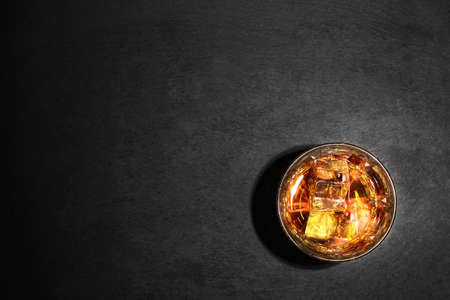 dark backgrounds: Glass of whiskey with ice on black background shot from above