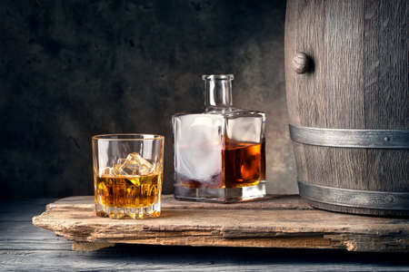 Glass of whiskey with ice decanter and barrel on wooden table Reklamní fotografie