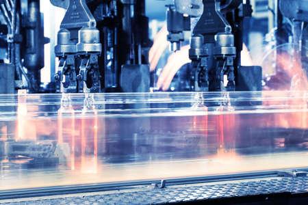 maquinaria: Mover la línea de montaje para la producción de botellas en tonos azul Foto de archivo