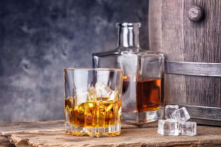 Whisky in glass and ice on the background of wooden barrels Standard-Bild