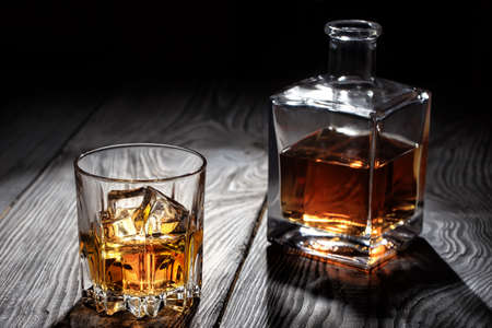 Backlit glass of whiskey with ice on wooden table Standard-Bild