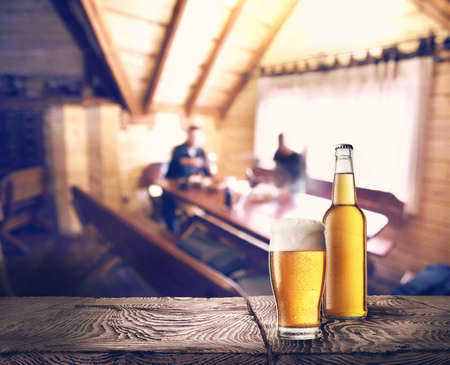 pilsner glass: Bottle and glass of beer on table against background of cafe Stock Photo