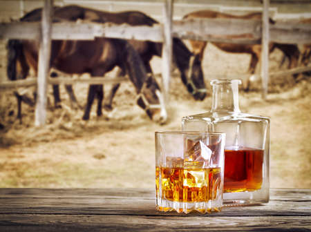 caballo bebe: Decanter and glass of whiskey on background of the ranch Foto de archivo