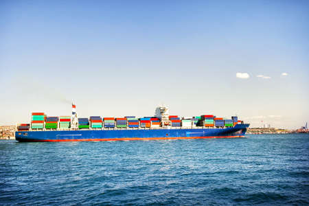 tranfer: Ship loaded with colorful containers in blue sea Stock Photo