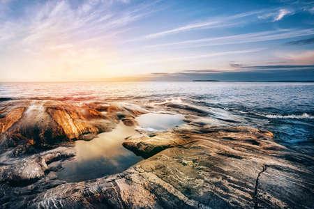 clear waters: Stone coast of Ladoga lake at sunset. Karelia, Russia. Stock Photo