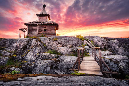 Old wooden church on island with bridge under dramatic sky