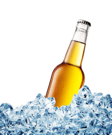 Yellow misted over bottle of beer on ice isolated on white background