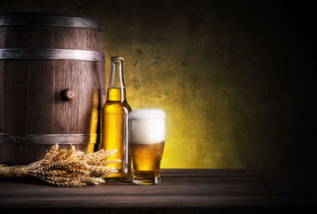 colored bottle: Glass of light beer with foam on background of bottles and barrels