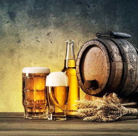 tinted glasses: Barrel and beer glasses on the table tinted in yellow and blue Stock Photo