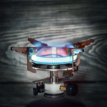 gas burner: The burning portable gas burner on wooden background